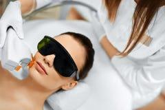 applicera genomskinlig fernissa för omsorgshud Framsidaskönhetbehandling IPL Fotoansiktsbehandlingterapi ansel Royaltyfria Bilder