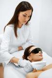 applicera genomskinlig fernissa för omsorgshud Framsidaskönhetbehandling IPL Fotoansiktsbehandlingterapi ansel Royaltyfri Fotografi