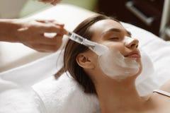 applicera genomskinlig fernissa för omsorgshud Härlig kvinna som får den kosmetiska maskeringen på den Spa salongen Royaltyfri Bild