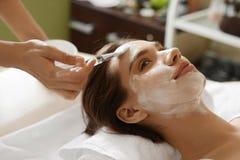 applicera genomskinlig fernissa för omsorgshud Härlig kvinna som får den kosmetiska maskeringen på den Spa salongen Royaltyfri Fotografi