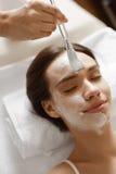 applicera genomskinlig fernissa för omsorgshud Härlig kvinna som får den kosmetiska maskeringen på den Spa salongen Royaltyfri Foto