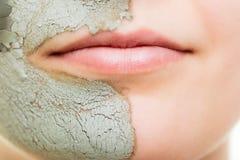 applicera genomskinlig fernissa för omsorgshud Kvinna i leragyttjamaskering på framsida _ Arkivfoto