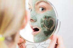 applicera genomskinlig fernissa för omsorgshud Kvinna i leragyttjamaskering på framsida _ Royaltyfri Fotografi
