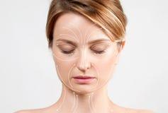 applicera genomskinlig fernissa för omsorgshud Kvinna med perfekt ren hud och ansikts- linjer för massage Royaltyfri Fotografi