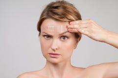 applicera genomskinlig fernissa för omsorgshud Kvinna med perfekt ren hud och ansikts- linjer för massage Royaltyfri Bild