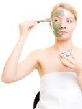 applicera genomskinlig fernissa för omsorgshud Kvinna som applicerar leragyttjamaskeringen på framsida Royaltyfri Foto