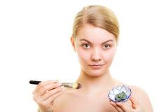 applicera genomskinlig fernissa för omsorgshud Kvinna som applicerar leragyttjamaskeringen på framsida Royaltyfri Fotografi