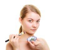 applicera genomskinlig fernissa för omsorgshud Kvinna som applicerar leragyttjamaskeringen på framsida Arkivfoto