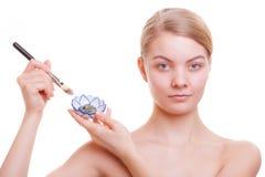 applicera genomskinlig fernissa för omsorgshud Kvinna som applicerar leramaskeringen på framsida Spa Arkivfoto
