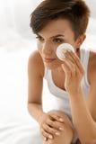 applicera genomskinlig fernissa för omsorgshud Kvinna som tar bort framsidamakeup som rentvår skönhetframsidan Arkivbilder