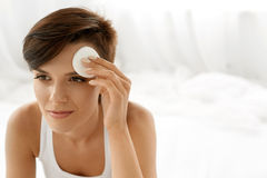 applicera genomskinlig fernissa för omsorgshud Kvinna som tar bort framsidamakeup som rentvår skönhetframsidan Arkivfoton