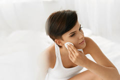 applicera genomskinlig fernissa för omsorgshud Kvinna som tar bort framsidamakeup som rentvår skönhetframsidan Royaltyfri Foto