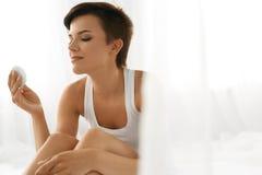 applicera genomskinlig fernissa för omsorgshud Kvinna som tar bort framsidamakeup som rentvår skönhetframsidan Arkivbild
