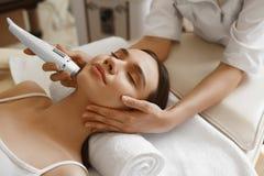 applicera genomskinlig fernissa för omsorgshud Kvinnor som analyserar ansikts- hud med analysatorn _ Royaltyfri Fotografi