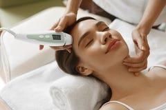 applicera genomskinlig fernissa för omsorgshud Kvinnor som analyserar ansikts- hud med analysatorn _ Arkivfoto