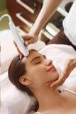 applicera genomskinlig fernissa för omsorgshud Kvinnor som analyserar ansikts- hud med analysatorn _ Royaltyfri Bild