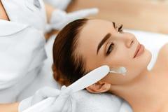 applicera genomskinlig fernissa för omsorgshud Skönhetsmedelkräm på kvinnas framsida Le ung kvinna med tumen upp Arkivfoton
