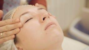 Applicera kräm på framsida och massera i skönhetsalongen arkivfilmer