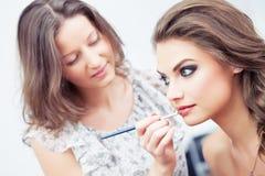 Applicera läppstift med en borste Royaltyfri Bild