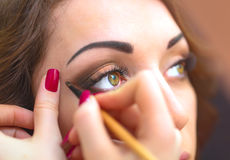 Applicera makeup, eyeliner på en härlig ålder-släkt kvinnaframsida Arkivfoton