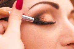 Applicera makeup, eyeliner på en härlig ålder-släkt kvinnaframsida Arkivbild