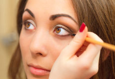 Applicera makeup, eyeliner på en härlig ålder-släkt kvinnaframsida Royaltyfri Foto