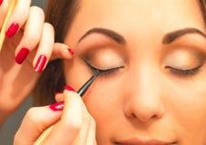 Applicera makeup, eyeliner på en härlig ålder-släkt kvinnaframsida Royaltyfri Bild