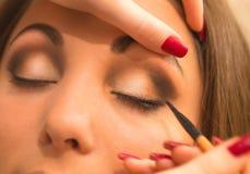 Applicera makeup, eyeliner på en härlig ålder-släkt kvinnaframsida Royaltyfria Bilder
