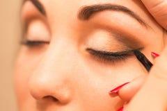 Applicera makeup, eyeliner på en härlig ålder-släkt kvinnaframsida Arkivbilder