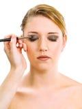 Applicera makeup på härlig modell Fotografering för Bildbyråer