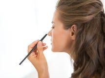 applicera makeupkvinnabarn Royaltyfri Bild