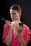 Applicera smink med en borste Royaltyfria Bilder