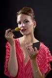 Applicera smink med en borste Royaltyfri Bild