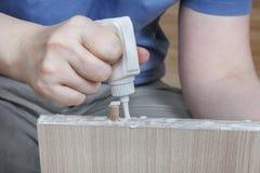 Applicera wood lim, snickare som limmar trädelar för möblemang, royaltyfri fotografi