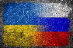 Applicerade ryss- och ukrainareflaggor som målas på betongväggen Arkivfoton