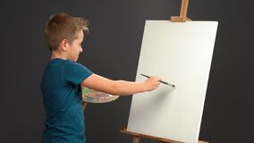 Free Applies A Stroke To The Canvas While Holding A Palette With Paints 10 Year Old Boy In Blue T-shirt Looks At Camera On Royalty Free Stock Image - 205780996