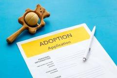 Applikation som adopterar barnet med leksaken på blå bakgrund arkivfoto