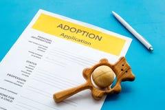 Applikation som adopterar barnet med leksaken på blå bakgrund royaltyfri fotografi