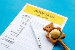 Applikation som adopterar barnet med leksaken på blå bakgrund royaltyfri foto
