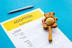 Applikation som adopterar barnet med leksaken p? bl? bakgrund arkivbild