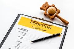 Applikation som adopterar barnet med leksaken p? vit bakgrund arkivfoto