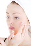 Appling crema sulla pelle del fronte fotografia stock