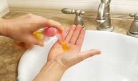 Appliquant le savon liquide avant de laver des mains Image stock