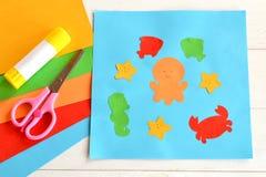 Applique de papel con los animales y los pescados de mar Lección del arte en guardería Hojas del papel coloreado, tijeras, pegame Fotografía de archivo libre de regalías