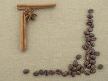 Appliquen från bönor grillat kaffe, kanelbruna pinnar och anis blommar på grov kanfasbeiga Arkivbilder