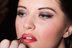 Appliquez le rouge à lèvres avec une brosse rouge Images libres de droits