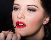 Appliquez le rouge à lèvres avec une brosse rouge Photo stock