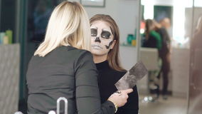 Apply make-up the girl in the form of skull. In full HD stock footage