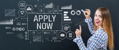 Apply now with young woman. Writing on a blackboard stock images