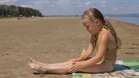 Apply sunscreen to face and body. The girl apply sunscreen to face and body. The girl squeezes the sunscreen into her palm and puts it on her feet stock images